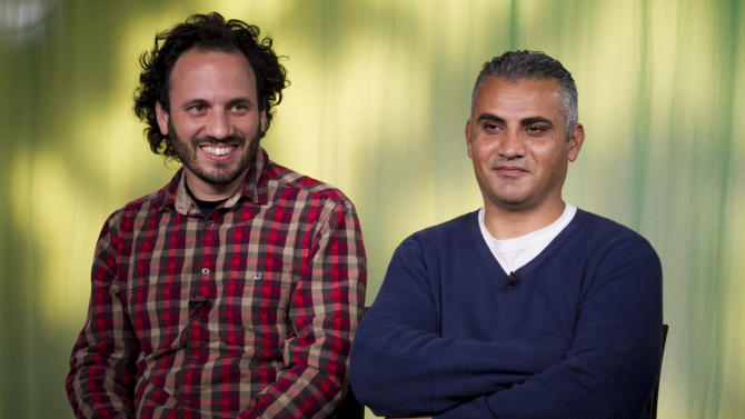 """In this Tues., Feb. 5, 2013 photo, documentary film Co-directors, Israeli, Guy Davidi, left, and Palestinian, Emad Burnat, pose for a photo after an interview in Los Angeles. Their 2011 documentary film, """"5 Broken Cameras,"""" is nominated for an Oscar in the best Documentary Feature category.  (AP Photo/Damian Dovarganes)"""