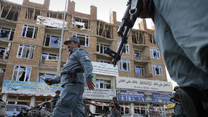 Afghan police officers past a building which was used by militants in a gun battle, near the Afghan parliament in Kabul, Afghanistan, Monday, April 16, 2012. A brazen, 18-hour Taliban attack on the Afghan capital ended early Monday when insurgents who had holed up overnight in two buildings were overcome by heavy gunfire from Afghan-led forces and pre-dawn air assaults from U.S.-led coalition helicopters. (AP Photo/Ahmad Jamshid)