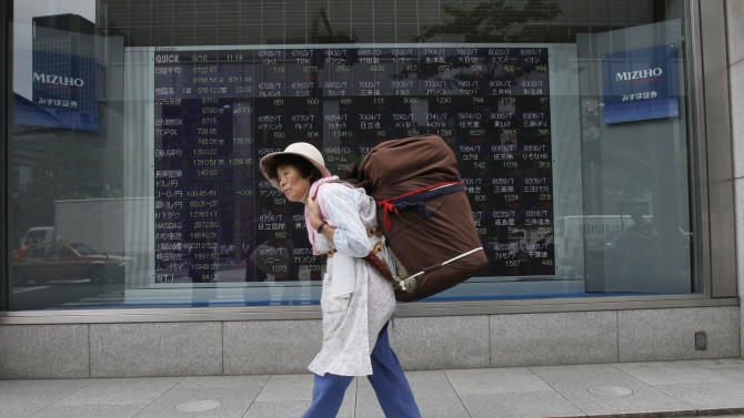 A woman walks by an electronic stock board of a securities firm in Tokyo, Monday, June 18, 2012. Asian stock markets climbed Monday after elections in Greece eased fears of global financial turmoil, but analysts warned that the economic crisis shaking the 17 nations in the euro common currency was far from over. Tokyo's benchmark Nikkei 225 index was up 1.8 percent at 8,721.41. (AP Photo/Koji Sasahara)