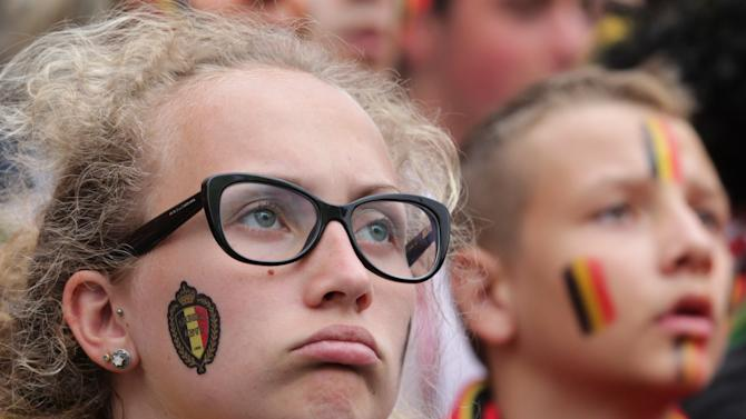 A fan of the Belgian national soccer team looks dejected while watching their quarterfinals soccer match against Argentina, broadcast on a video screen in front of the King Baudouin stadium in Brussels, Saturday, July 5, 2014. Argentina defeated Belgium 1-0. (AP Photo/Yves Logghe)