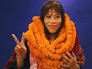 Indian women's boxing champion and Olympic bronze medal winner Mary Kom, wearing marigold garlands presented by well-wishers, gestures during a reception in New Delhi on August 14. A Bollywood film-maker is working on a movie about Kom, who has become a national hero