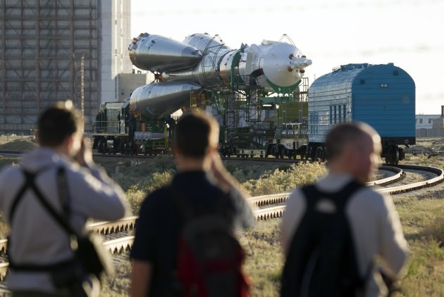 Photographers take pictures of the Soyuz TMA-09M spacecraft as it is transported to its launch pad at Baikonur cosmodrome
