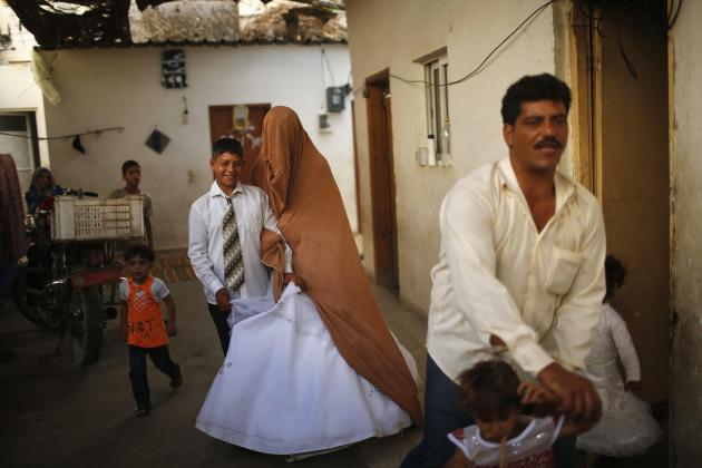Young Palestinian bride Soboh and groom Ahmed leave Tala's house, which was damaged during Israeli strike in 2009, during wedding party in Beit Lahiya