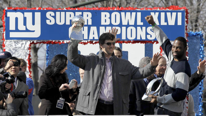 New York Giants quarterback Eli Manning, center, holding the Vince Lombardi Trophy and defensive end Justin Tuck, right, holding the Halas Trophy,  wave to the crowd during a ticker-tape parade celebrating the team's NFL Super Bowl XLVI championship, Tuesday, Feb. 7, 2012, in New York. The Giants beat the New England Patriots 21-17 on Sunday, Feb. 5, in Indianapolis. (AP Photo/Julio Cortez)