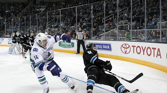 San Jose Sharks defenseman Justin Braun (61) is tripped by Vancouver Canucks center Alex Burrows (14) during the second period of an NHL hockey game in San Jose, Calif., Sunday, Jan. 27, 2013. (AP Photo/Tony Avelar)