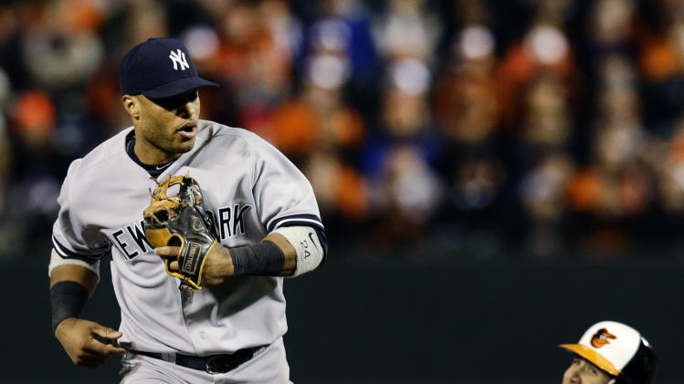 New York Yankees second baseman Robinson Cano, left, jogs off the field after forcing out Baltimore Orioles' Manny Machado, back, at second on a ground ball by Robert Andino to end the fourth inning of Game 2 of the American League division baseball series on Monday, Oct. 8, 2012, in Baltimore. (AP Photo/Alex Brandon)
