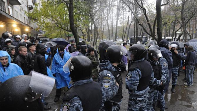Riot police separate opposition and pro-government activists outside an election precinct in Kiev where the opposition alleged election fraud in Kiev, Ukraine, Friday, Nov. 2, 2012. Nearly a week after Ukraine's parliamentary election, officials on Friday still scrambled to tally votes in several key districts across the country, in what the opposition says is a clear example of widespread vote rigging by the ruling party. As the vote-counting dragged on in one Kiev precinct, fists flew, tear gas was fired, opposition activists shouted angrily and an election official sobbed hysterically.  (AP Photo/Sergei Chuzavkov)