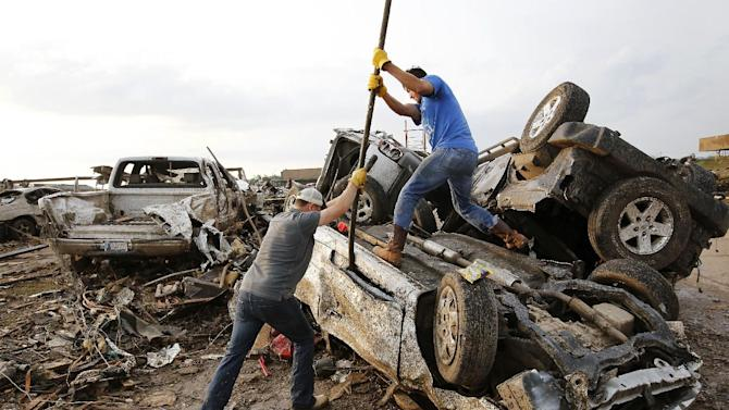 Two men attempt  to pry open a door on this car to check for victims in a business parking lot west of I-35 south of 4th Street  in Moore, on Monday, May 20, 2013.A monstrous tornado roared through the Oklahoma City suburbs, flattening entire neighborhoods with winds up to 200 mph, setting buildings on fire and landing a direct blow on an elementary school. (AP Photo/The Oklahoman, Jim Beckel)