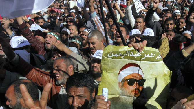 """Supporters of Sheik Omar Abdel-Rahman, a blind Egyptian cleric jailed in the United States for planning a campaign of bombings, call for his release  while one demonstrator holding a poster with his image, during a rally outside Cairo University in Cairo, Egypt, Friday, Feb. 15, 2013. Around 5,000 mostly hardline Islamists are rallying in Egypt against a recent wave of protests that has killed around 70 people. Arabic reads, """"Omar Abdel-Rahman."""" (AP Photo/Amr Nabil)"""