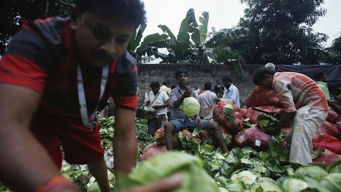 Vendors sort out cabbages along a road outside a wholesale vegetable market at dawn in Mumbai