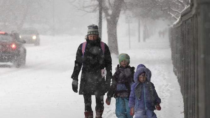 Linda Jones walks her daughters Sophie and Zoe to school as a blizzard dropped snow over Boulder, Colo., Wednesday Dec. 19, 2012. A storm that has dumped more than a foot of snow in the Rocky Mountains is heading east and is forecast to bring the first major winter storm of the season to the central plains and Midwest. (AP Photo/Brennan Linsley)