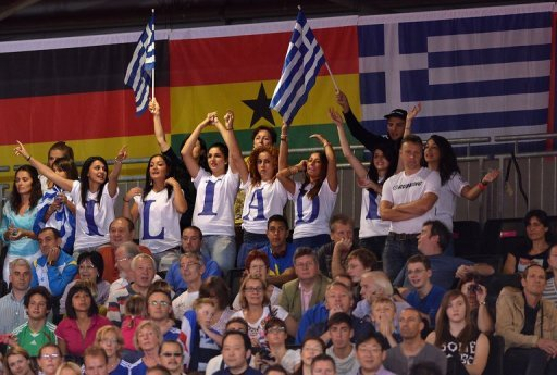 Fans of Greece's Ilias Iliadis cheer during the men's -90kg judo contest at the ExCel arena in London