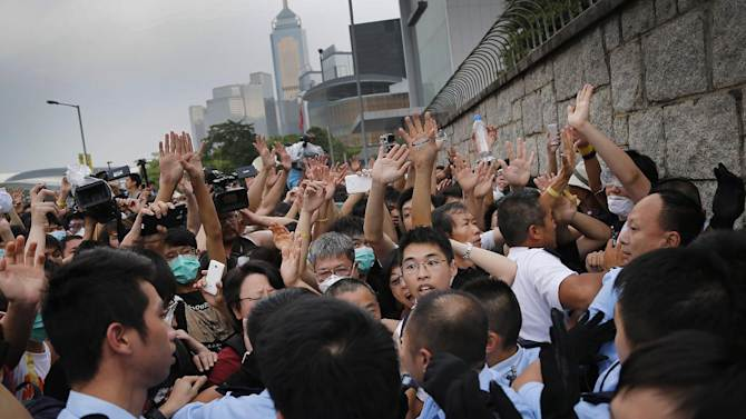 Student protesters resist during change of shift for local police but backed down after being reassured they could reoccupy the pavement outside the government compound's gate, Thursday, Oct. 2, 2014 in Hong Kong. Hong Kong police warned of serious consequences if pro-democracy protesters try to occupy government buildings, as they have threatened to do if the territory's leader doesn't resign by Thursday. (AP Photo/Wong Maye-E)