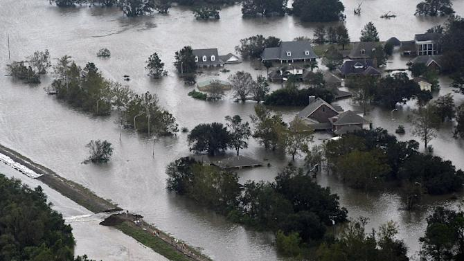 This aerial photo shows an intentional levy breach created to alleviate trapped floodwater in the community of Braithwaite, La., in the aftermath of Isaac, Thursday, Aug. 30, 2012. Isaac soaked Louisiana for yet another day and pushed more water into neighborhoods all around the city, flooding homes and forcing last-minute evacuations and rescues. (AP Photo/Gerald Herbert)