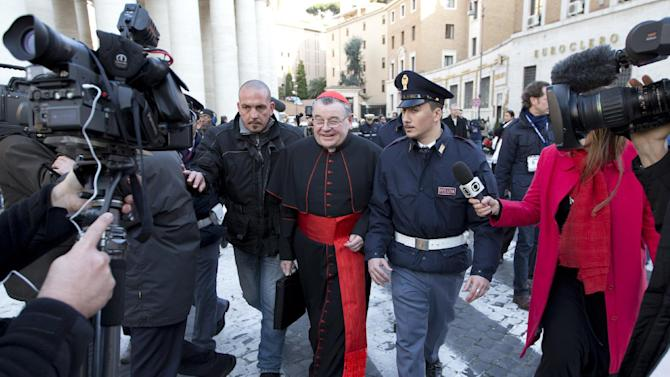 """FILE - This March 4, 2013 file photo shows Cardinal Dominik Duka, of the Czech Republic, is escorted by police, surrounded by journalists, as he arrives for a cardinals' meeting, at the Vatican, Monday, March 4, 2013. These are crazy days in Rome - where limbo reigns in parliament and papacy. Italy is usually a pretty anarchic place, with people bucking rules on everything from crossing the street to paying taxes. But the anarchy's going a bit far: Who's running the country? Who's running the church? Nobody really knows. We Romans are living truly surreal times when a bearded comedian whose surname means """"cricket"""" is now one of the nation's most powerful leaders, and aging cardinals from around the world are mobbed by paparazzi as if they were Hollywood starlets.  (AP Photo/Andrew Medichini)"""
