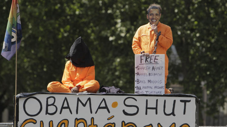 FILE - In this May 25, 2011 file photo, protesters, both dressed in an orange overalls, depicting detainees at the U.S. military detention centre in Guantanamo, Cuba, one hooded and one holding a mask depicting U.S. President Barack Obama, demonstrates outside Britain's Houses of Parliament, in central London, where Obama was to give an address. Obama's rock-star-like reception at Berlin's Victory Column in the summer of 2008 was a high point of a wildly successful European campaign tour. Those high European expectations have turned into disappointment, largely because of the continued U.S. military presence in Iraq and Afghanistan and Obama's failure to close Guantanamo Bay in the face of vehement congressional opposition. (AP Photo/Lefteris Pitarakis, File)
