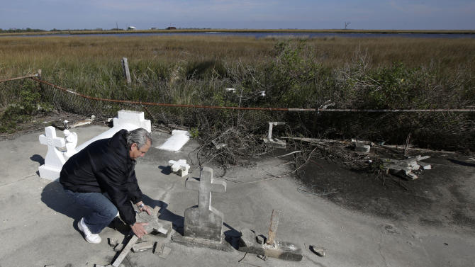 In this Dec. 29, 2012 photo, South Lafourche Levee District General Manager Windell Curole, who also serves on the state's Coastal Protection and Restoration Authority, handles pieces of headstone at his small family cemetery which sits along the bayou near Leeville, La. Some 11 cemeteries in Jefferson Parish have repeatedly flooded since Katrina, and in Lafourche, Terrebonne and Plaquemines parishes, more than a dozen others have succumbed to tidal surges. Curole said saltwater from the Gulf is causing a crippling subsidence problem. (AP Photo/Dave Martin)