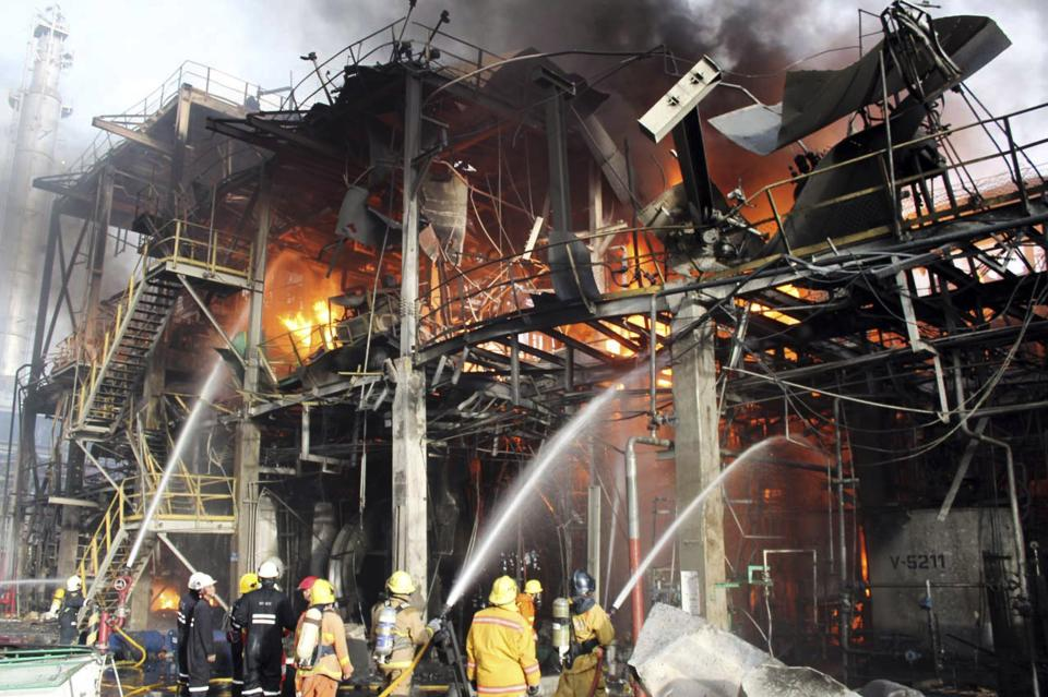 In this photo taken Saturday, May 5, 2012, Thai firefighters try to put off the fire after an explosion at a factory in Rayong province, Thailand. A fire caused by explosions in one of the world's largest petrochemical industrial estates have killed 12 and injured more than 100 people in eastern Thailand. (AP Photo)