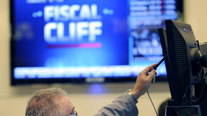 """FILE - In this Nov. 7, 2012, file photo, James Dresch of MND Partners Inc. works on the floor of the New York Stock Exchange in New York. Stocks declined for a third day on Wall Street Wednesday, Nov. 28, 2012,  as investors waited for signs of progress on the """"fiscal cliff."""" (AP Photo/Henny Ray Abrams, File)"""