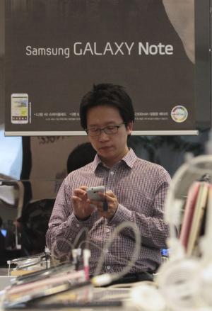 A shopper tries out Samsung Electronics' smart phone Galaxy at its showroom in Seoul, South Korea, Friday, April 27, 2012. Samsung Electronics Co., the world's largest consumer electronics firm by revenues, on Friday reported a record-high profit as strong smartphone sales helped mask a drop in semiconductor and TV profit. Net profit amounted to 5.05 trillion won ($4.46 billion) for the fiscal quarter ending March 31, compared with 2.78 trillion won a year earlier. (AP Photo/Ahn Young-joon)