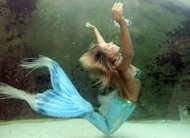 """File photo of Hannah the Mermaid in the Mermaid Lagoon exhibit at the Sydney Aquarium. The United States government has assured citizens that much like zombies, mermaids probably do not exist. """"Mermaids -- those half-human, half-fish sirens of the sea -- are legendary sea creatures."""" (AFP Photo/Torsten Blackwood)"""