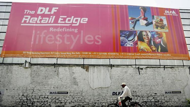 A man rides pass an advertisement of Indian property developer DLF Ltd. in Mumbai