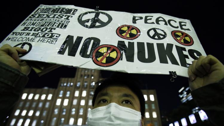 An anti-nuclear protester holds up a placard in front of a branch of Kansai Electric Power Co, the operator of the Ohi nuclear power plant which has been shut down, in Tokyo