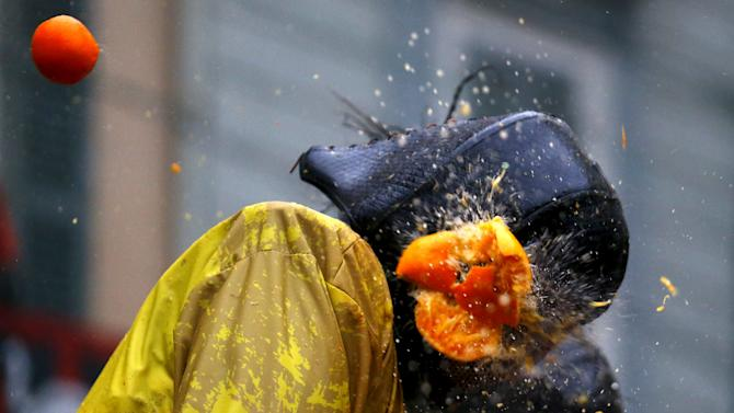 A member of a rival team is hit by an orange during an annual carnival battle in the northern Italian town of Ivrea