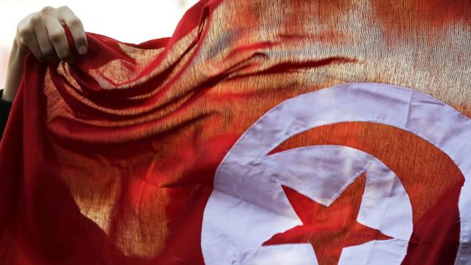 File photo of a person holding up a Tunisian flag and shouts slogans during celebrations marking the fourth anniversary of Tunisia's 2011 revolution, in Habib Bourguiba Avenue in Tunis
