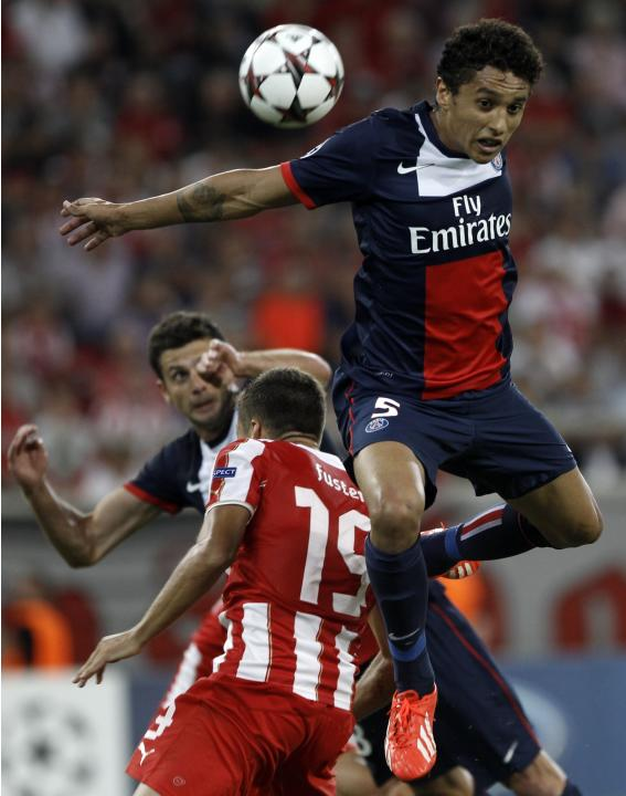 Paris St Germain's Marquinhos jumps for the ball during the Group C Champions League soccer match against Olympiakos in Piraeus
