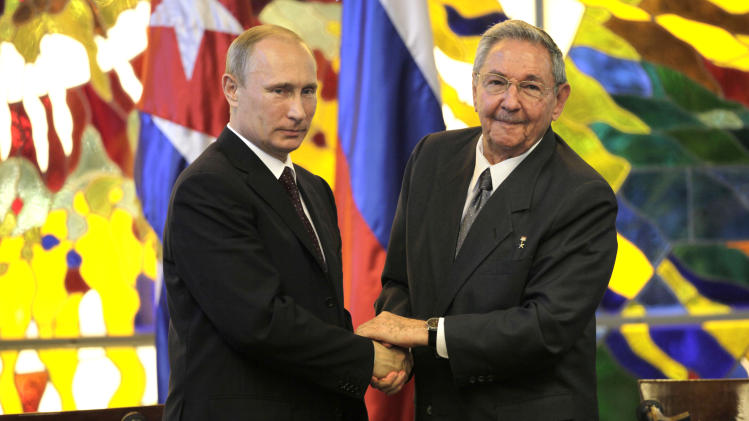 Cuba's President Raul Castro, right, shakes hands with Russia's President Vladimir Putin at Revolution Palace in Havana, Cuba, Friday, July 11, 2014. Putin began a Latin American tour aimed at boosting trade and ties in the region with a stop Friday in Cuba, a key Soviet ally during the Cold War that has backed Moscow in its dispute with the West over Ukraine. (AP Photo/Ismael Francisco, Cubadebate)