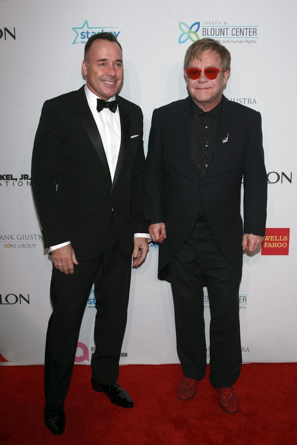 "David Furnish and Elton John arrive at the Elton John AIDS Foundation's 12th Annual ""An Enduring Vision"" benefit gala at Cipriani Wall Street on Tuesday, Oct. 15, 2013, in New York. (Photo by Carlo Allegri/Invision/AP)"