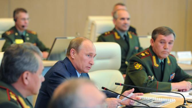 """Russian President Vladimir Putin, second left, has a meeting in the Russian Armed Forces main operational center  in Moscow, Russia, Thursday, June 6, 2013. At right is Chief of the armed forces' General Staff Gen. Valery Gerasimov. and at left is Defense Minister Sergei Shoigu. President Vladimir Putin says Russia will permanently keep a navy squadron in the Mediterranean Sea to protect its interests. Speaking at Thursday's meeting with the military brass, Putin said the move shouldn't be interpreted as saber-rattling. He said the Mediterranean is a """"strategically important region, where we have interests connected with ensuring Russia's national security."""" (AP Photo/RIA-Novosti, Mikhail Klimentyev, Presidential Press Service)"""