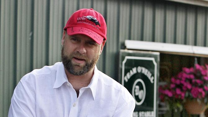 FILE - In this May 16, 2012, file photo, Kentucky Derby-winning trainer Doug O'Neill talks outside his barn at Pimlico Race Course in Baltimore. O'Neill was suspended 45 days on Thursday, May 24, by the California Horse Racing Board as a result of one of his horses exceeding the allowable limit for total carbon dioxide. But the punishment won't begin before July 1, ensuring he will be able to saddle I'll Have Another in next month's Belmont Stakes. (AP Photo/Garry Jones, File)