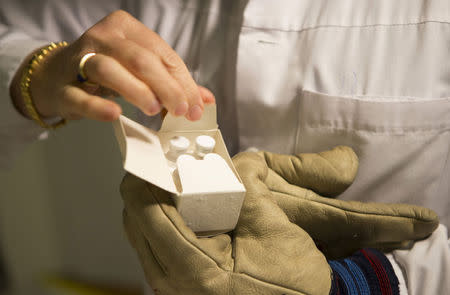 A medical staff holds a package of an experimental candidate vaccine rVSV-ZEBOV against Ebola virus disease at the University hospital in Geneva