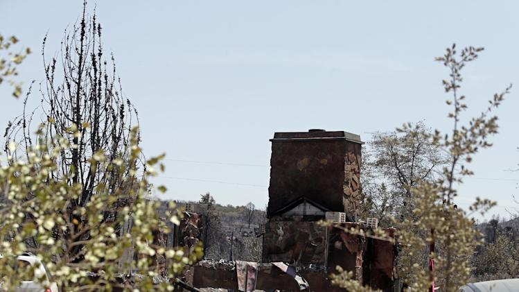 A burned home is left ruined near Yarnell, Ariz., Wednesday, July 3, 2013. An elite crew of firefighters was overtaken by the out-of-control blaze on Sunday, killing 19 members as they tried to protect themselves from the flames under fire-resistant shields. (AP Photo/Chris Carlson)