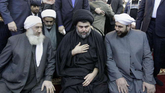 Firebrand Shiite cleric Muqtada al-Sadr, center, is welcomed by Sunni clerics at Abdul-Qadir al-Gailani Sunni mosque in Baghdad, Iraq, Friday, Jan. 4, 2013. Al-Sadr paid a visit Friday to a Baghdad church that was the scene of a deadly 2010 attack as well as one of the Iraqi capital's main Sunni mosques, an apparent overture to other religious groups as opposition mounts against his rival, Prime Minister Nouri al-Maliki. (AP Photo/ Khalid Mohammed)