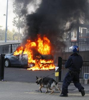 A Police dog and its handler walk past a burning car during the second night of civil disturbances in central Birmingham, England, Tuesday, Aug. 9, 2011. Britain began flooding London's streets with 16,000 police officers Tuesday, nearly tripling their presence as the nation feared its worst rioting in a generation would stretch into a fourth night. The violence has turned buildings into burnt out carcasses, triggered massive looting and spread to other U.K. cities. (AP Photo/Tim Hales)