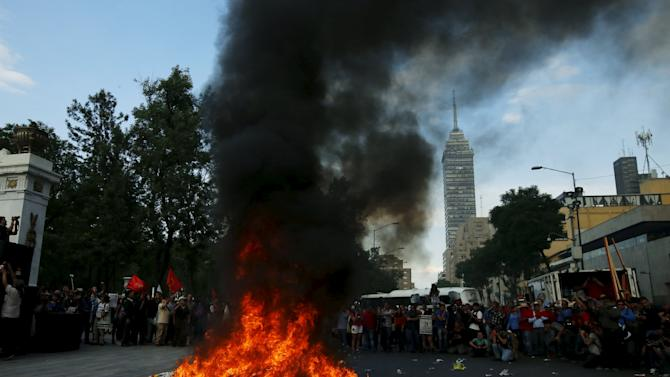 Demonstrators gather around burning posters of political candidates during a protest to mark the eight-month anniversary of the Ayotzinapa students' disappearance in Mexico City