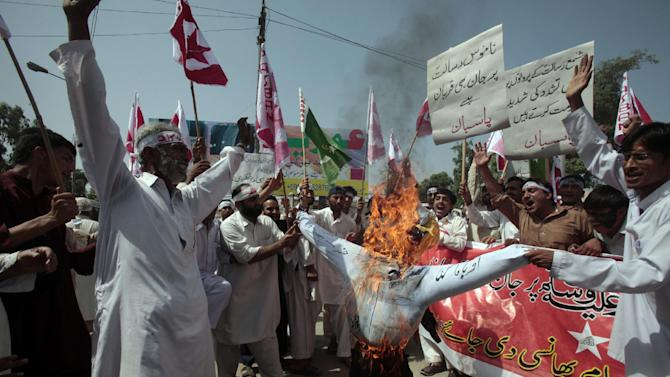 "Pakistani protesters burn an effigy of U.S. President Barack Obama during a demonstration that is part of widespread anger across the Muslim world about a film ridiculing Islam's Prophet Muhammad, near the  US consulate in Peshawar, Pakistan on Tuesday, Sept. 18, 2012. Placard reads, ""ready to die for the sanctity of the Prophet."" (AP Photo/Mohammad Sajjad)"