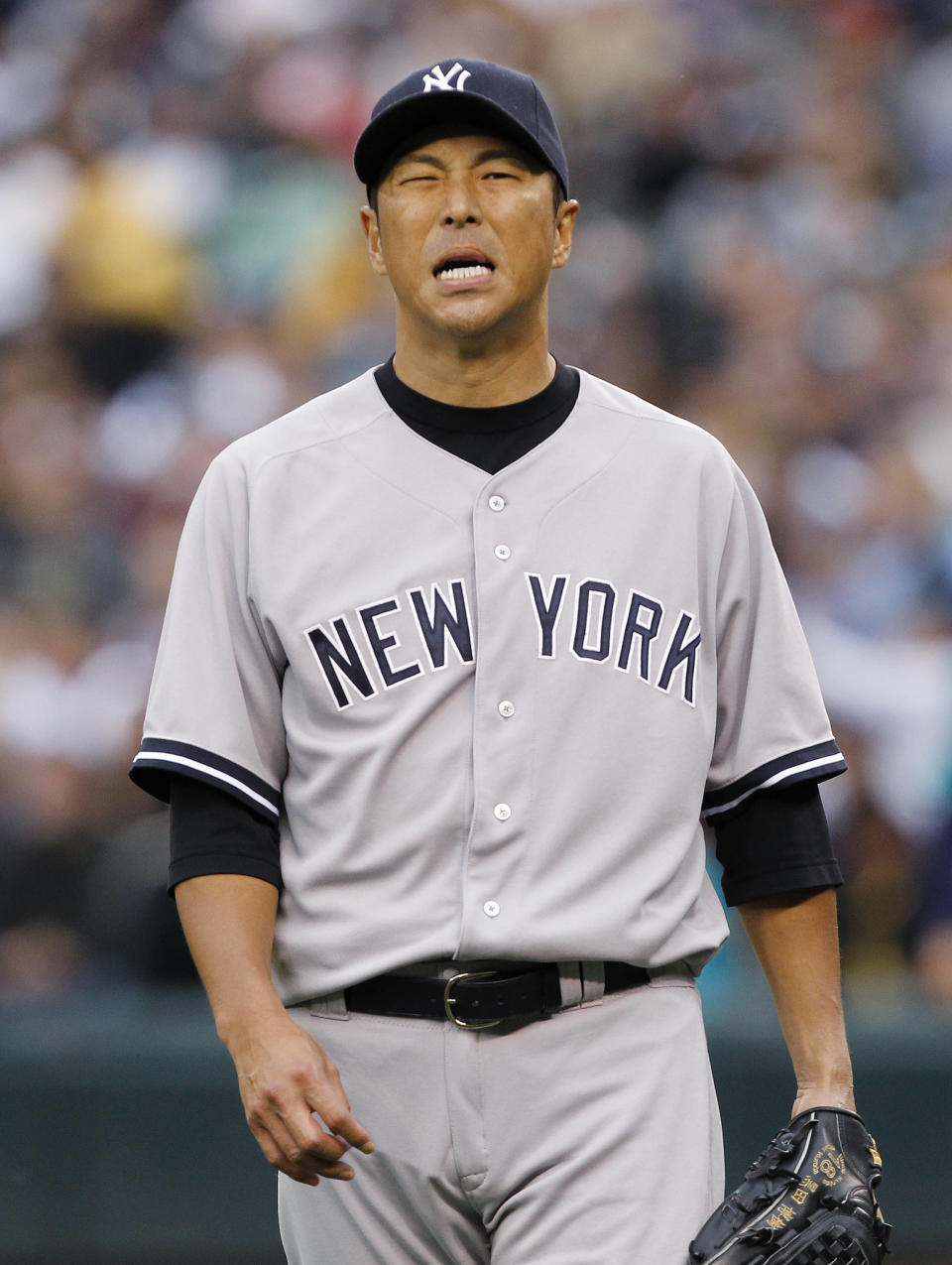 New York Yankees starting pitcher Hiroki Kuroda reacts after giving up a hit to the Seattle Mariners in the first inning of a baseball game Monday, July 23, 2012, in Seattle. (AP Photo/Elaine Thompson)