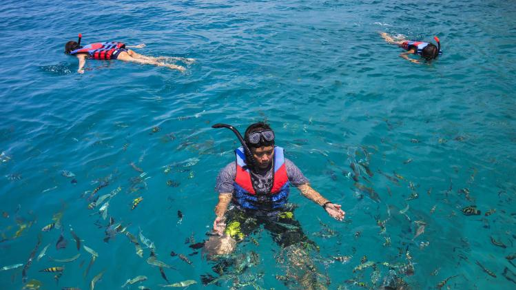 Tourists swim in clear water near Kut island in eastern Thailand