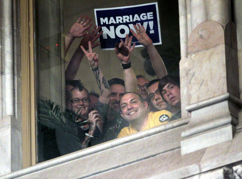 People watch from a window in the Senate Chamber as Senators passed a gay marriage bill at the Capitol in Albany, N.Y., on Friday, June 24, 2011.  (AP Photo/Mike Groll)