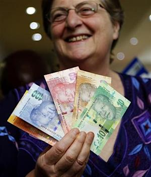 South African Reserve Bank Governor Gill Marcus smiles as she shows off South Africa's new banknotes before conducting the first transaction in Pretoria