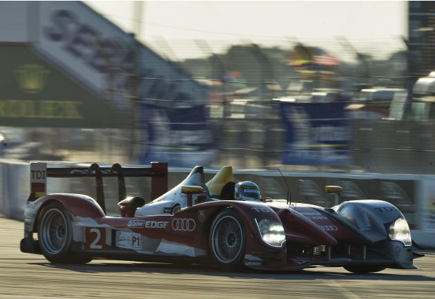 Audi Sport Team Joest's Allan McNish, of Scotland, steers the Audi R15+ TDI through Turn 1 before sunset during the 59th annual American Le Mans Series 12 Hours of Sebring auto race at the Sebring Int