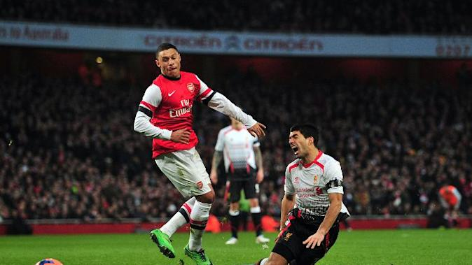 Liverpool's Uruguayan striker Luiz Suarez (R) is brought down by Arsenal's English striker Alex Oxlade-Chamberlain (L) at The Emirates Stadium in north London on February 16, 2014