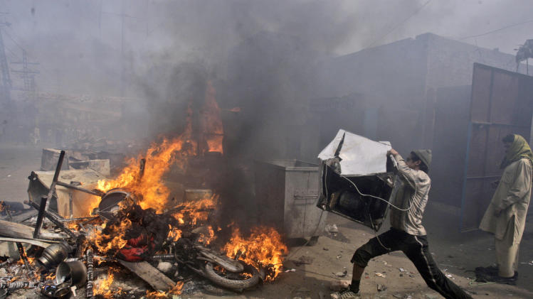 A Pakistani man, part of an angry mob, throws items taken from Christian houses into a fire in Lahore, Pakistan, Saturday, March 9, 2013. A mob of hundreds of people in the eastern Pakistani city of Lahore attacked a Christian neighborhood Saturday and set fire to homes after hearing accusations that a Christian man had committed blasphemy against Islam's prophet, said a police officer. (AP Photo/K.M. Chaudary)