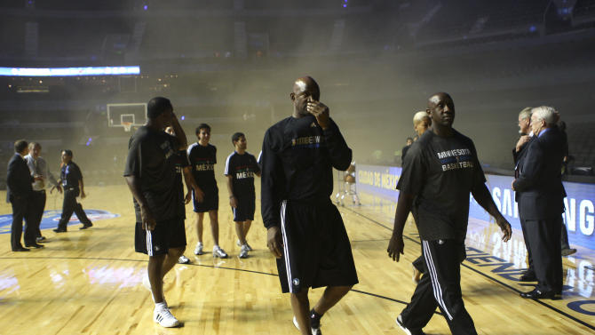 Members of the Minnesota Timberwolves evacuate The Mexico City arena in Mexico City, Wednesday, Dec. 4, 2013. The NBA says the game between the San Antonio Spurs and Minnesota Timberwolves has been postponed because of smoky conditions inside the Mexico City arena. The arena was evacuated about 45 minutes before the scheduled tipoff when a generator malfunction outside the arena sent smoke pouring into the building, an NBA spokeswoman says. (AP Photo/Christian Palma)