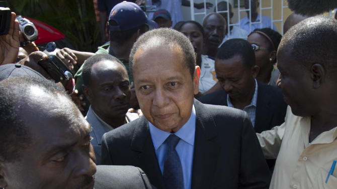 FILE - In this March 29, 2011 file photo, former Haitian dictator Jean-Claude Duvalier, center, leaves Canape Vert hospital in Port-au-Prince, Haiti. Duvalier has spurned a judge's order to appear in court, Thursday, Feb. 21, 2013, for a hearing on whether to reinstate charges of human rights abuses against him. (AP Photo/Dieu Nalio Chery, File)