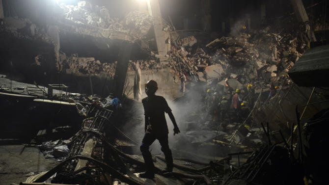 A worker leaves the site where a garment factory building collapsed near Dhaka, Bangladesh Monday, April 29, 2013. Rescue workers in Bangladesh gave up hopes of finding any more survivors in the remains of a building that collapsed five days ago, and began using heavy machinery on Monday to dislodge the rubble and look for bodies - mostly of workers in garment factories there. At least 381 people were killed when the illegally constructed, 8-story Rana Plaza collapsed in a heap on Wednesday morning along with thousands of workers in the five garment factories in the building. (AP Photo/Ismail Ferdous)